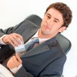 Confident businessman sitting at office desk and putting money in pocket — Stock Photo #8653908