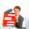 Confused businessman sitting at office desk with pile of folders — Stock Photo #8653996