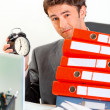 Dissatisfied businessman sitting at office desk with pile of folders and ho — Stock Photo