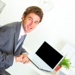 Pleased businessman  sitting at office desk and  showing yes ges — Stock Photo