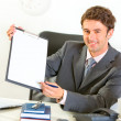 Stock Photo: Smiling businessmgiving clipboard and pen for signing