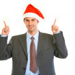 Smiling young businessman in Santa hat pointing finger up — Stock Photo #8654260