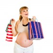 Happy pregnant woman holding shopping bags in hands — Stock Photo #8655577