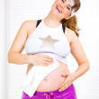 Laughing beautiful pregnant woman wiping her belly with towel after exercis - Stockfoto
