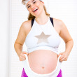 Happy beautiful pregnant female in sportswear with towel around her belly - Stockfoto