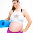 Smiling beautiful pregnant woman in sportswear with exercise mat - Stockfoto