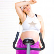 Pregnant womsitting on stationary bicycle and relaxing after work out — Stock Photo #8656345