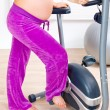 Stock Photo: Beautiful pregnant female training on exercise bike