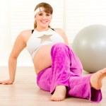 Smiling beautiful pregnant woman making gymnastics at home — Stock Photo