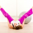 Smiling beautiful pregnant woman doing stretching exercises at home — Stock Photo