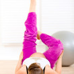 Smiling beautiful pregnant female making gymnastics at living room — Stock Photo