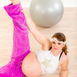 Stock Photo: Beautiful pregnant female doing stretching exercises at home