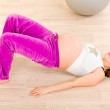 Smiling beautiful pregnant female doing fitness exercises at home — Stock Photo