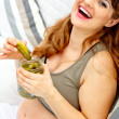 Pregnant woman relaxing on sofa at home and holding jar of pickles in hands — Stock Photo