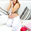 Pregnant female sitting on sofa at home with gifts for her unborn baby - Stock Photo