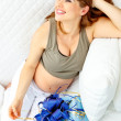 Pregnant female sitting on sofat home with gifts for her unborn baby — Stock Photo #8656802