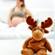 Toy lying on table and pregnant female sitting on sofa  in background — Stock Photo