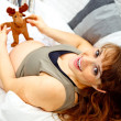 Happy beautiful pregnant woman lying on sofa and holding toy. Close-up. — Stock Photo #8656920