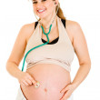 Smiling pregnant woman holding stethoscope on her belly - Stok fotoğraf