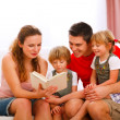 Stock Photo: Mother and father reading to twins daughters
