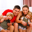 Mom and dad playing with twins daughter on console — Stock Photo