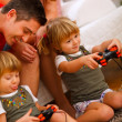 Twins daughters playing on console at home — Stockfoto