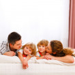 Family portrait of mom dad and twins daughters on bed — Stock Photo