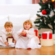 Two happy twins girl sitting with presents under Christmas tree — Stock Photo