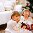 One of twins girl sitting with present with serious expression — Stock Photo #8657871