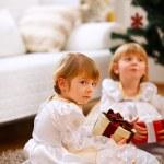 una chica de gemelos sentado con presente con expresión grave — Foto de Stock