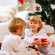 Two twins girl sitting with presents near Christmas tree — Stock Photo #8657873