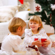 Royalty-Free Stock Photo: Two twins girl sitting with presents near Christmas tree