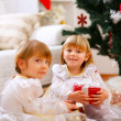 Two girls sitting with presents near Christmas tree — Stock Photo