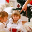 Hand of parent pointing on present to twins girl — Stock Photo