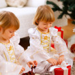 Two happy twins girl opening presents near Christmas tree — 图库照片