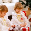 Two happy twins girl opening presents near Christmas tree — Stockfoto #8657886