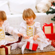 Two happy twins girl opening presents near Christmas tree — Stock Photo #8657888