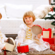 Two smiling twins girl opening presents near Christmas tree — Stock Photo #8657889