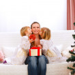 Two twins daughters presenting gift to mother and kissing her — Stock Photo