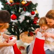 Mom and dad looking with twins daughters inside of Christmas socks — Stockfoto