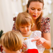 Mother looking with twins daughters inside of Christmas socks — Stock Photo #8657908