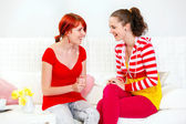 Two laughing girlfriends sitting on sofa and looking each other — Stock Photo