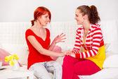 Duas namoradas bonitas, sentado no sofá e falando — Fotografia Stock