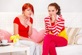 Two surprised girlfriends sitting on sofa — Stock Photo