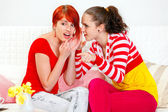 Young girl whispering gossips in ear of her interested girlfriend and point — Stock Photo