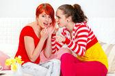 Mladá dívka šeptá přihazovat v uchu její zájem přítelkyni a bodu — Stock fotografie