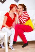 Pretty girl whispering gossips in ear of her interested girlfrie — Stock Photo