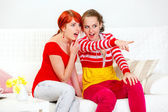 Cheerful girl sitting on sofa and showing something to her girlfriend — Φωτογραφία Αρχείου