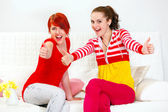 Two smiling girlfriends sitting on sofa and showing thumbs up gesture — Stock Photo