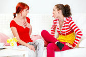 Funny girl sitting on sofa and showing tongue her amazed girlfriend — Stock Photo